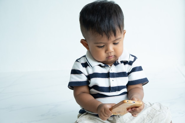Schattige kleine aziatische babyjongen spelen slimme telefoon