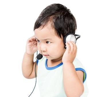 Schattige kleine aziatische jongen en moderne hoofdtelefoon