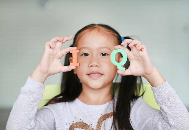 Schattige kleine aziatische kind meisje houdt van alfabetletters op haar gezicht