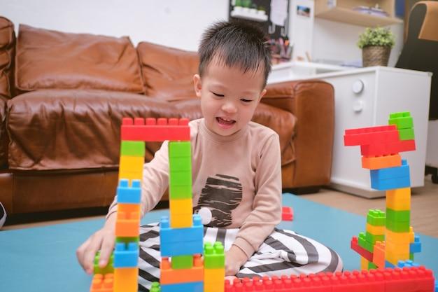 Schattige kleine aziatische kleuterschool jongen spelen blokken met kleurrijke plastic blokken binnen thuis