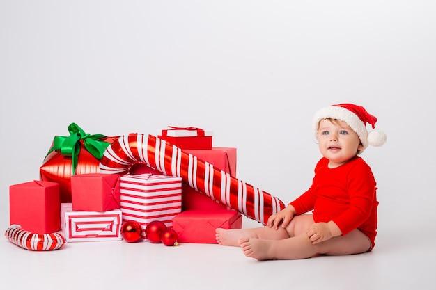Schattige kleine baby in een kerstkostuum met geschenken