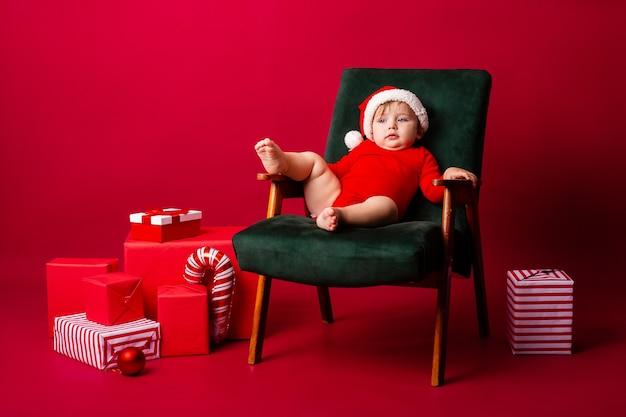 Schattige kleine baby in een kerstkostuum op een stoel