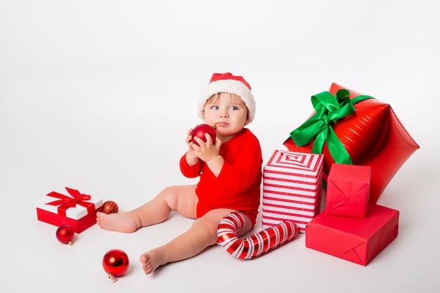 Schattige kleine baby in een kerstman kostuum met geschenken