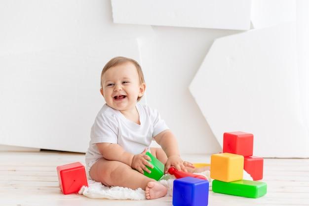Schattige kleine baby in een wit t-shirt en luiers spelen thuis op een mat met felgekleurde blokjes