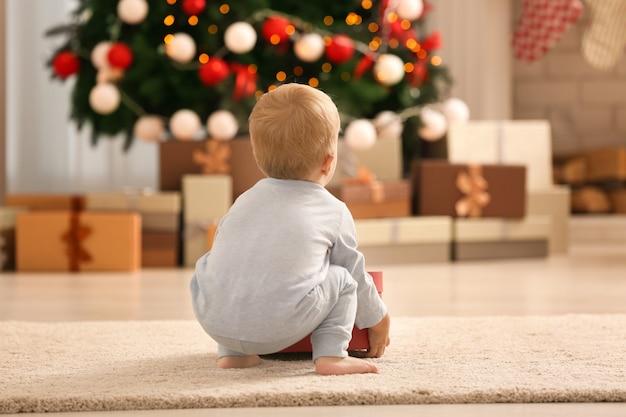 Schattige kleine baby in kamer versierd voor kerstmis