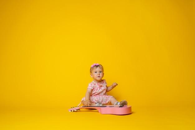 Schattige kleine baby, in roze jurk gitaarspelen op geel