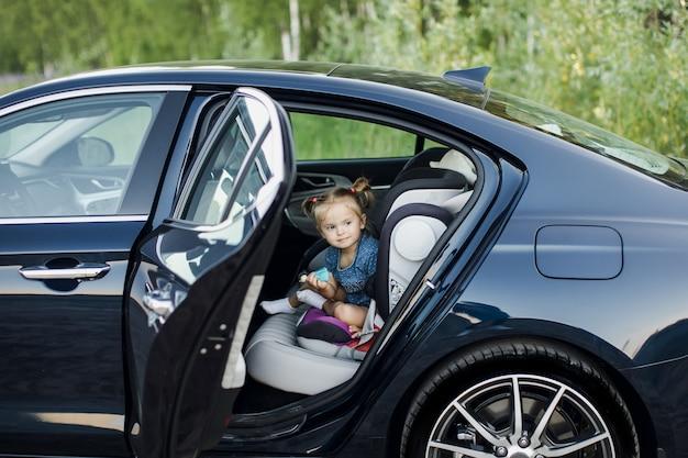 Schattige kleine baby kind zitten in autostoel