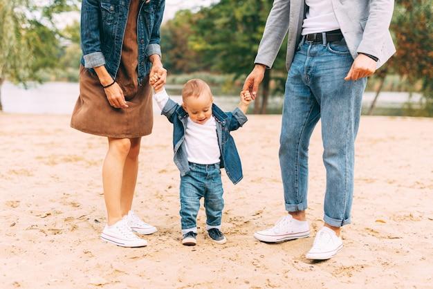 Schattige kleine baby leert lopen in de buurt van zijn ouders op zand bij een meer