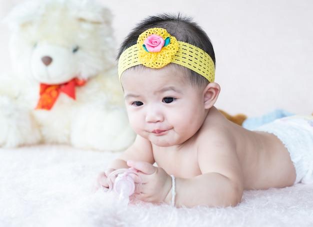 Schattige kleine baby liggend gelukkig houden uitsteeksel fopspeen in de hand