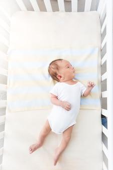 Schattige kleine baby liggend in witte wieg op zonnige dag