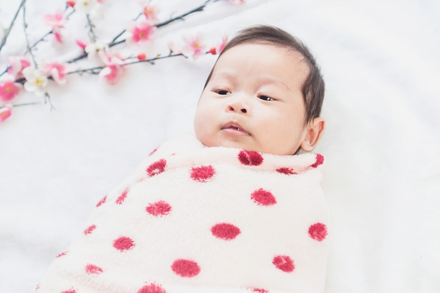 Schattige kleine baby ligt op een witte doek en gewikkeld in een quilt