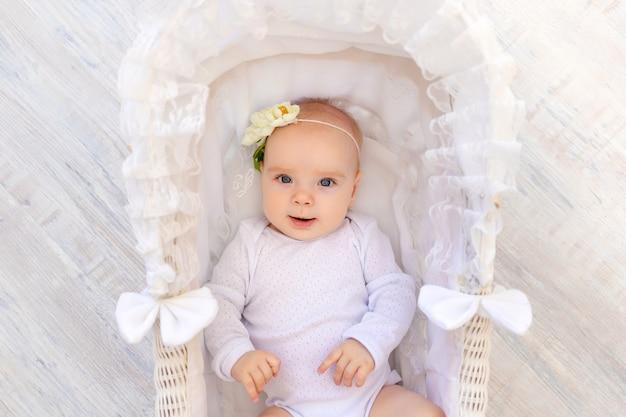 Schattige kleine baby meisje in een witte romper ligt in een mooie wieg babybed