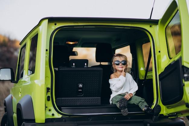 Schattige kleine baby meisje zit in de rug zitten van de auto