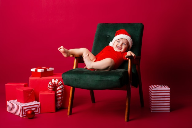 Schattige kleine baby met een kerstmuts op een stoel