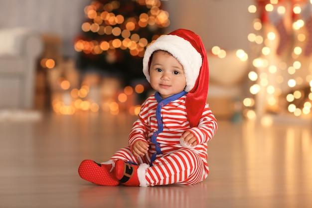 Schattige kleine baby met kerstmuts op de vloer en wazige kerstverlichting op het oppervlak