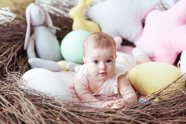 Schattige kleine baby met kleurrijke paaseieren en speelgoed konijn liggend in het nest.