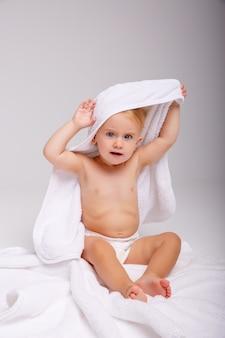 Schattige kleine baby met zachte handdoek op witte achtergrond