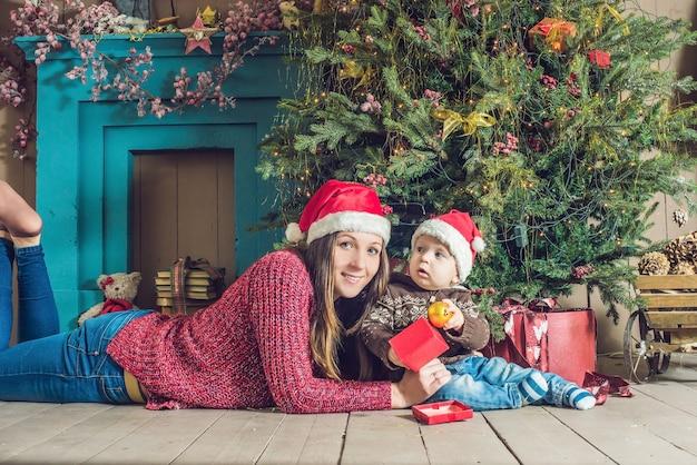 Schattige kleine baby met zijn moeder zit in de buurt van de kerstboom