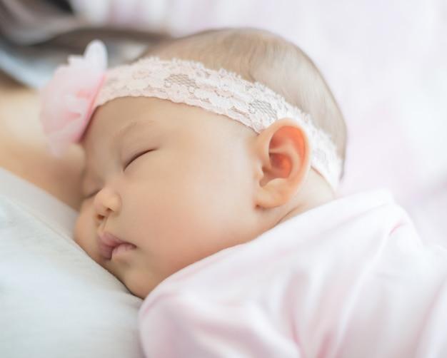 Schattige kleine baby op slapen op de borst van moeders.
