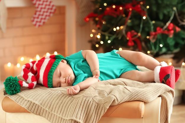 Schattige kleine baby slaapt tegen het wazige oppervlak van de kerstverlichting