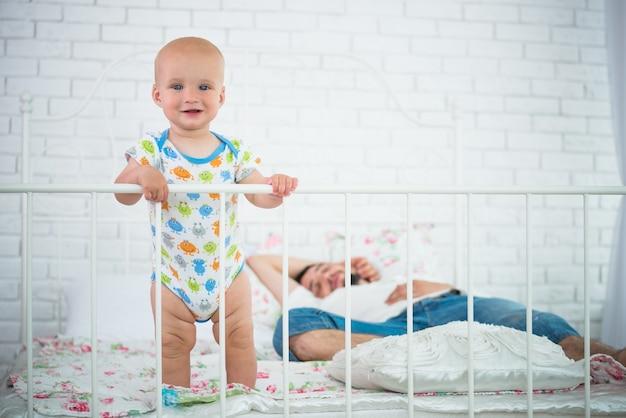 Schattige kleine baby staat op de rand van het bed en houdt zich vast aan het hoofdeinde tegen de achtergrond