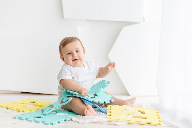 Schattige kleine baby van zes maanden oud in een wit t-shirt en luiers die thuis spelen op een mat in een lichte kamer