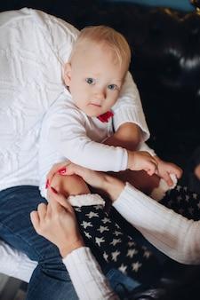 Schattige kleine baby wordt gestreeld door zijn liefhebbende ouders terwijl hij zachte kerstsokken aan heeft. vakantie concept