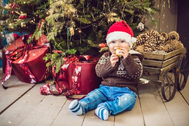 Schattige kleine baby zit in de buurt van de kerstboom