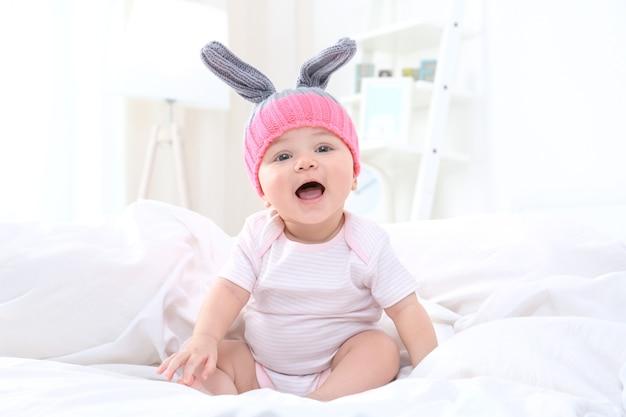 Schattige kleine baby zittend op bed thuis
