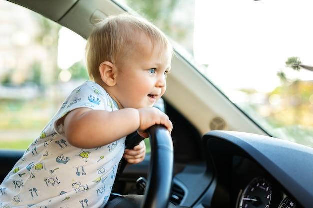 Schattige kleine babyjongen die grote auto bestuurt, stuur vasthoudt, glimlacht en met belangstelling uitkijkt. jeugdspel en dromen. copyspace