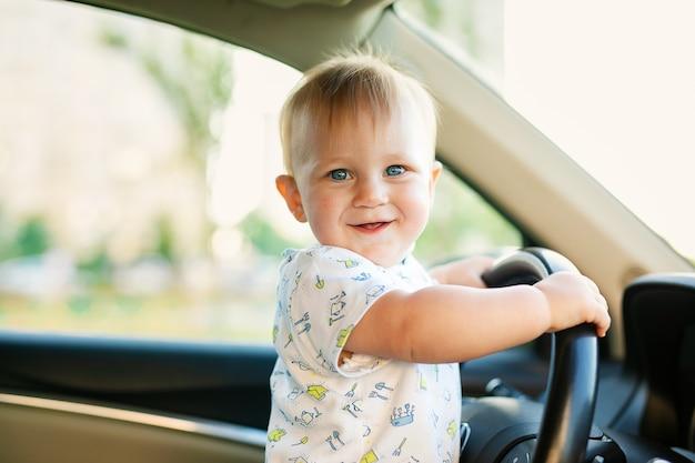 Schattige kleine babyjongen die grote auto bestuurt, stuur vasthoudt, glimlacht en met belangstelling uitkijkt. jeugdspel en dromen.