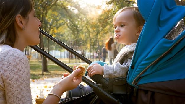 Schattige kleine babyjongen eten en kijken naar zijn moeder in herfst park.