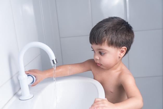 Schattige kleine babyjongen hand wassen in de badkamer wastafel