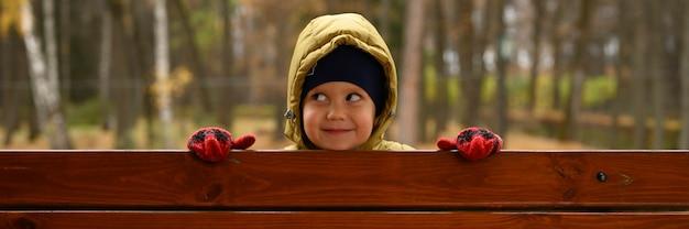 Schattige kleine babyjongen heeft plezier in de herfst park met zijn gezin op een zonnige herfstdag