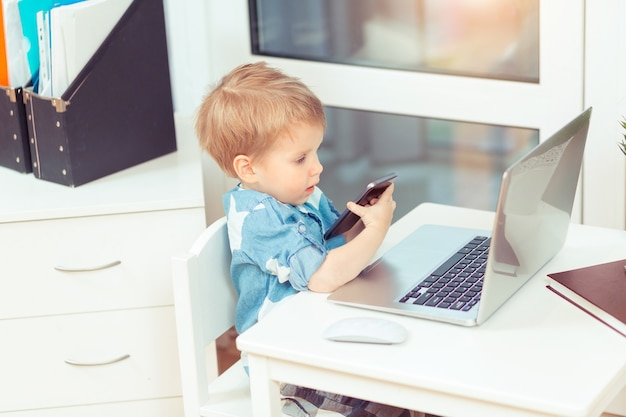 Schattige kleine babyjongen met computer laptop en mobiele telefoon op kantoor aan huis gadgets en kid concept