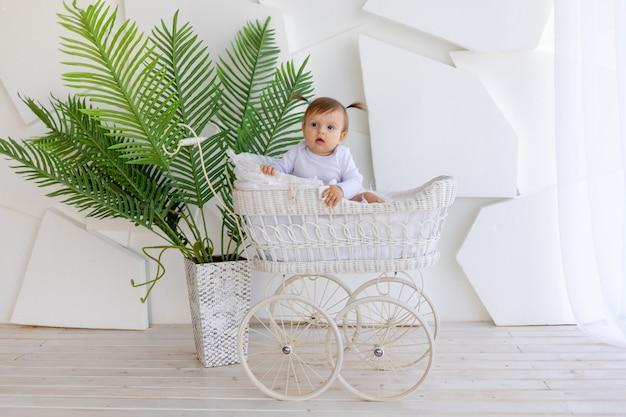 Schattige kleine babymeisje, zittend in een mooie wandelwagen in een witte romper thuis