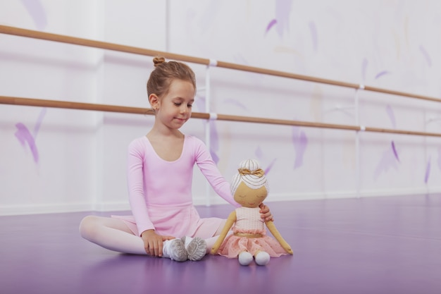 Schattige kleine ballerina die zich uitstrekt alvorens ballet op dansschool te oefenen, die naast haar pop zit, exemplaarruimte