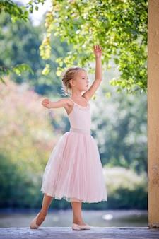 Schattige kleine ballerina in een delicate roze jurk staat in een sierlijke pose