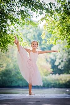 Schattige kleine ballerina in een roze jurk in de zomer buiten