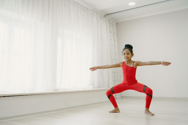 Schattige kleine ballerina in rode spotsuit. kind dansen in de kamer. kid in dansles.