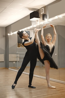 Schattige kleine ballerina in zwart balletkostuum. jonge dame danst in de kamer. meisje in dansles met leraar.
