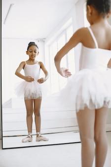 Schattige kleine ballerina. kind dansen in de kamer. kid in dansles.