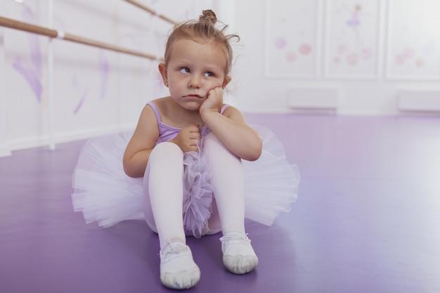 Schattige kleine ballerina op zoek moe en verveeld op balletles
