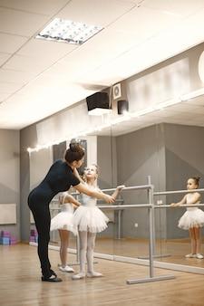 Schattige kleine ballerina's in roze balletkostuum. kinderen in spitzen dansen in de kamer. kid in dansles met leraar.