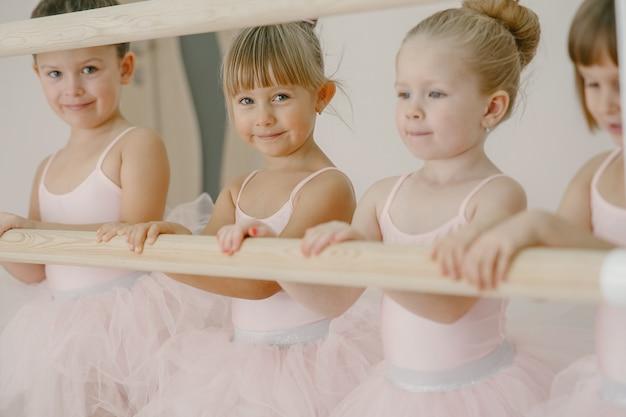 Schattige kleine ballerina's in roze balletkostuum. kinderen in spitzen dansen in de kamer. kid in dansles.