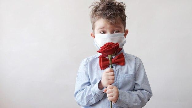 Schattige kleine blanke jongen in vlinderdas met rode roos in beschermend gezichtsmasker. valentijnsdag. covid.