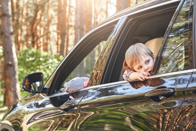 Schattige kleine blanke jongen zit in de auto en kijkt uit het raam familieweg