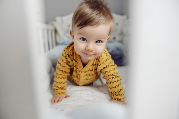 Schattige kleine blonde babyjongen met mooie blauwe ogen glimlachend en kruipen in wieg. ochtend tijd.