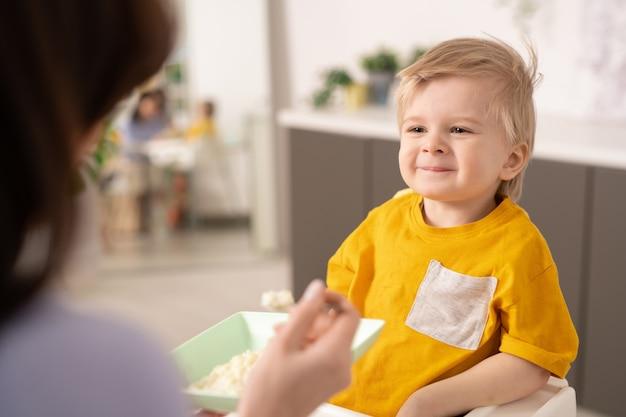 Schattige kleine blonde jongen die met een glimlach naar zijn moeder kijkt terwijl hij aan een kleine eettafel zit en zelfgemaakte pap als ontbijt heeft