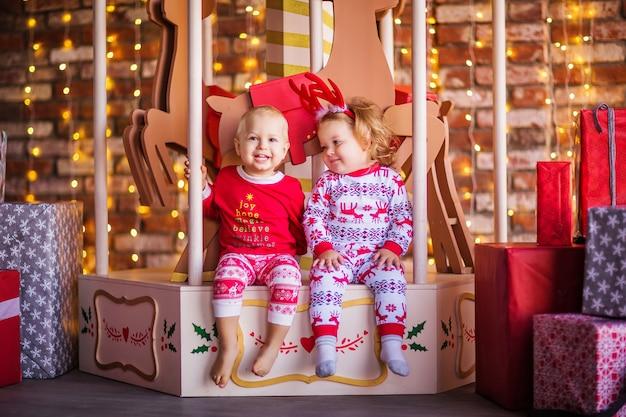 Schattige kleine blonde jongen en meisje zittend op de kerstcarrousel omringd door kerstcadeaus. hoge kwaliteit foto